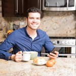 Good looking hispanic guy using a mobile phone while eating breakfast in kitchen